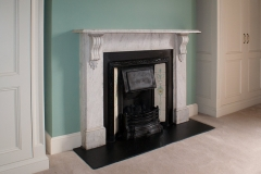 An antique carrara marble corbel fireplace with Victorian tiled insert.