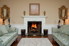 Antique carved pine fireplace painted white with Irish peat buckets made by Ryan & Smith